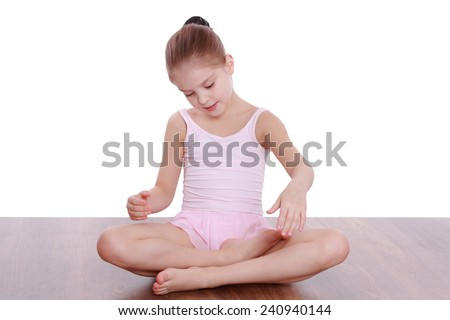 Portrait of a cute happy little girl doing gymnastic exercises on the floor - stock photo