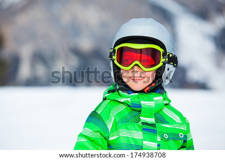 Portrait of a cute happy skier boy in a winter ski resort. - stock photo
