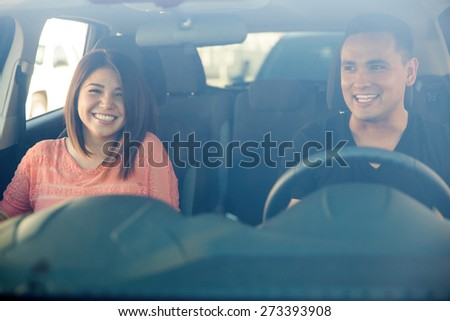 Portrait of a cute Hispanic couple having fun in a car, seen through the windshield - stock photo