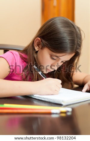 Portrait of a cute hispanic girl working on her school homework - stock photo