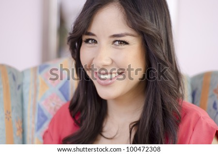 Portrait of a cute hispanic hairdresser in a salon - stock photo