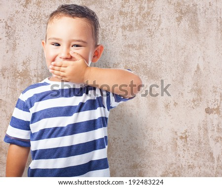 portrait of a cute kid covering his mouth with his hand - stock photo