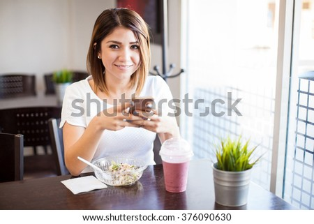 Portrait of a cute Latin woman updating her social media status on her smartphone while having lunch at a restaurant - stock photo