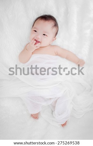 Portrait of a cute little baby on a white fur bed - stock photo