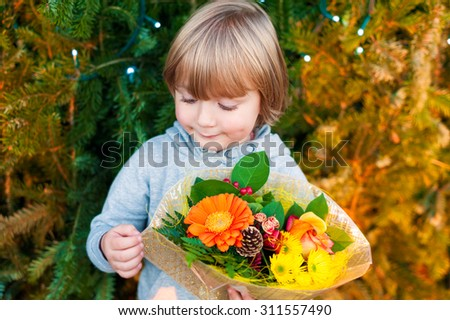 Portrait of a cute little boy holding christmas flower bouquet, standing next to christmas tree - stock photo