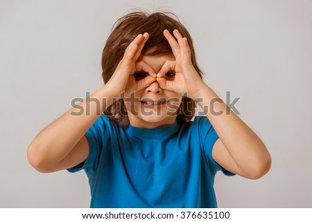 Portrait of a cute little boy in a blue t-shirt  showing eyeglasses with his hands, looking in camera and smiling while standing on a gray background - stock photo