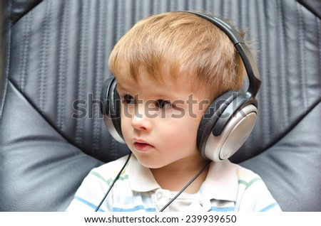 Portrait of a cute little boy in headphones - stock photo