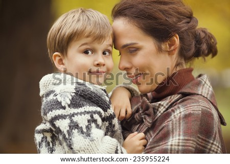 Portrait of a cute little boy in his mother's arms - stock photo