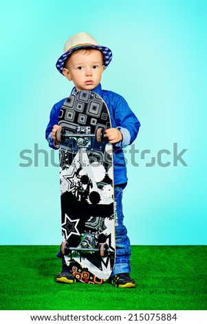 Portrait of a cute little boy in jeans clothes standing with a skateboard. Fashion. Childhood.