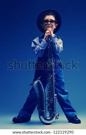Portrait of a cute little boy jazzman playing his saxophone. Retro style. - stock photo