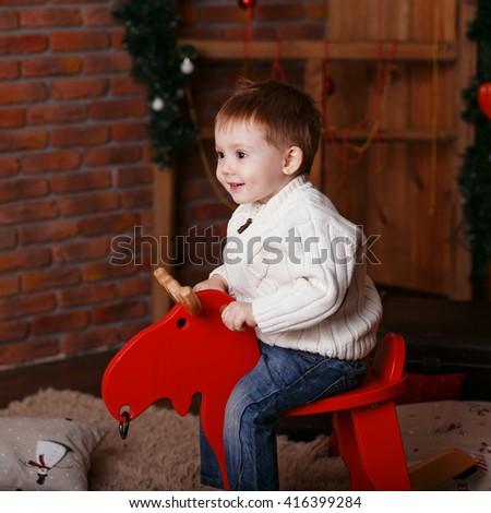 Portrait of a cute little boy. Little boy among Christmas decorations. Boy riding a rocking deer. Rocking deer chair for kids ride playing - stock photo