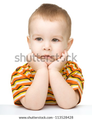 Portrait of a cute little boy looking at something while supporting his head with both hands, isolated over white