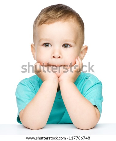 Portrait of a cute little boy looking at something while supporting his head with both hands, isolated over white - stock photo