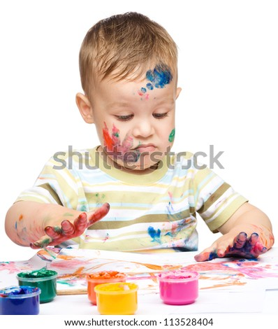 Portrait of a cute little boy messily playing with paints making funny grimace, isolated over white
