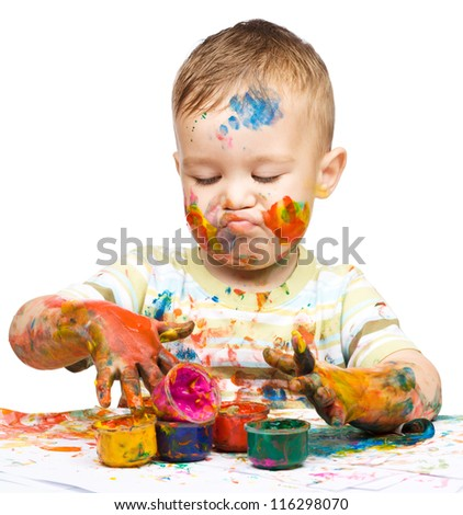 Portrait of a cute little boy messily playing with paints while making funny grimace, isolated over white