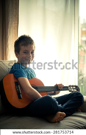 Portrait of a cute little boy posing with guitar - stock photo
