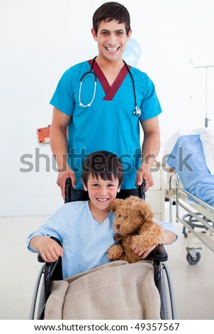 Portrait of a cute little boy sitting on wheelchair and a doctor at the hospital - stock photo