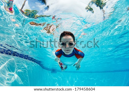 Portrait of a cute little boy swimming underwater - stock photo