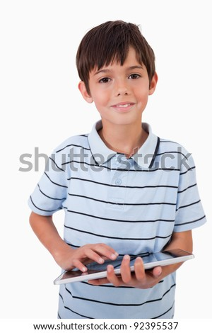 Portrait of a cute little boy using a tablet computer against a white background - stock photo