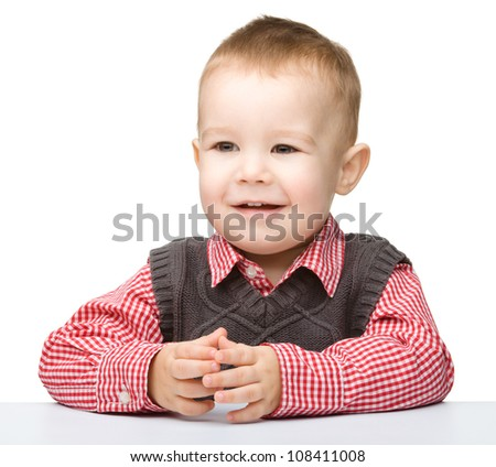 Portrait of a cute little boy, who is smiling while sitting at table, isolated over white