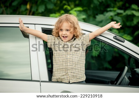 Portrait of a cute little boy who sitting in the car at the day time