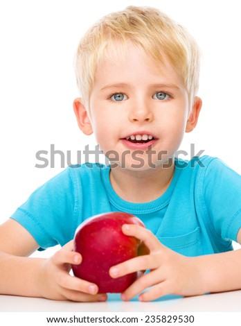 Portrait of a cute little boy with red apple, isolated over white - stock photo