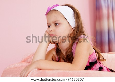 portrait of a cute little girl at couch