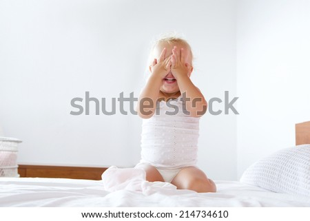 Portrait of a cute little girl hiding with hands covering face - stock photo