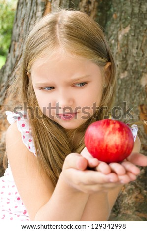 Portrait of a cute little girl holding red apple outdoors