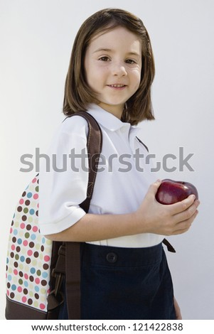 Portrait of a cute little girl in a school uniform holding an apple isolated over white background - stock photo
