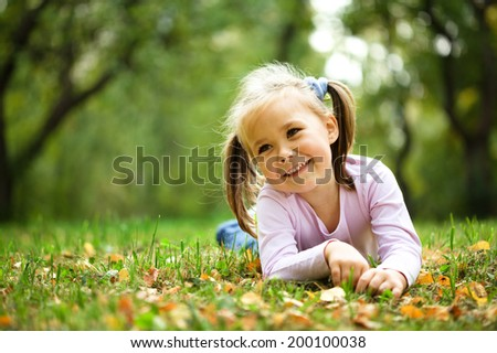 Portrait of a cute little girl in autumn park - stock photo