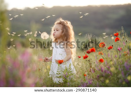 Portrait of a cute little girl in sunny summer day at green nature background. Summer joy - lovely girl blowing dandelion.  - stock photo