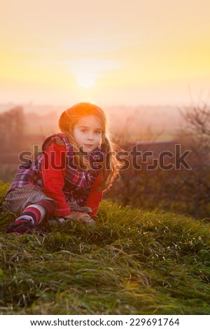 Portrait of a cute little girl in the warm light of an autumnal sunset in Sweden - stock photo