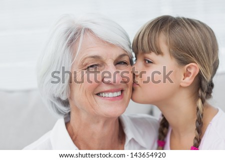 Portrait of a cute little girl kissing her grandmother - stock photo