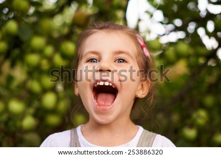 Portrait of a cute little girl making an excited face with her mouth wide open - stock photo