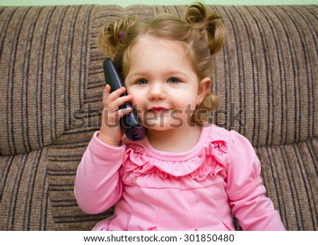 portrait of a cute little girl on chair talking on the phone and watch on viewer - stock photo