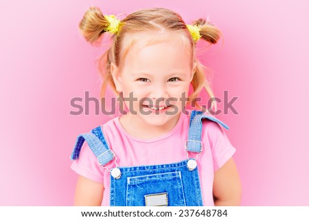 Portrait of a cute little girl over bright pink background. Happy childhood. - stock photo