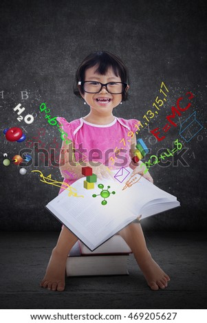 Portrait of a cute little girl sitting on the books while smiling at the camera and read book with formula of science, math, and physics