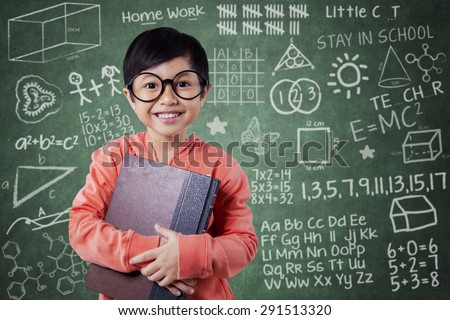 Portrait of a cute little girl standing in the classroom while holding textbook near the blackboard - stock photo