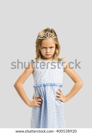 Portrait of a cute little girl with a princess crown making a sad face - stock photo
