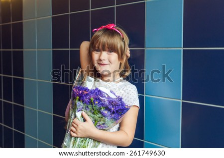 Portrait of a cute little girl with bouquet of aster autumn flowers - stock photo
