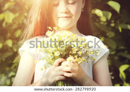 Portrait of a cute little girl with daisies  - stock photo