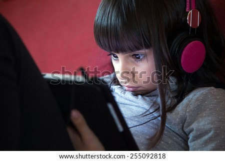Portrait of a cute little girl with headphones using a tablet pc at home - stock photo