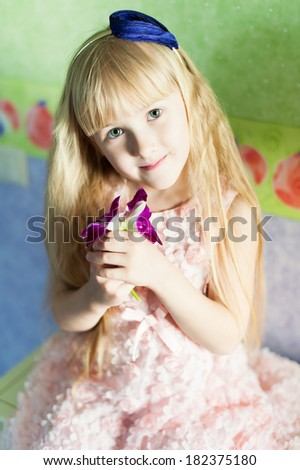 portrait of a cute little girl with long hair and flowers in her hands