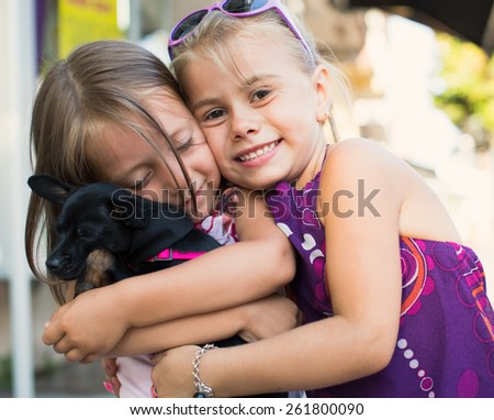 portrait of a cute little girls with dog outdoors - stock photo