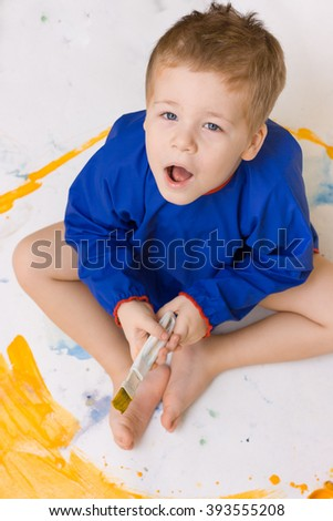 Portrait of a cute little kid boy sitting on the floor and drawing yellow sun. Young adorable child drawing. Small painter. Artist and bright colors. Creative activities with children indoors. Fun - stock photo