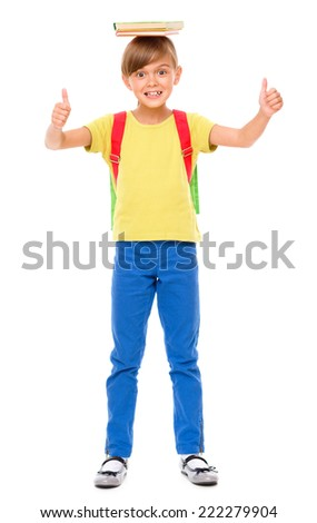 Portrait of a cute little schoolgirl with backpack holding book on her head and showing thumb up sign, isolated over white - stock photo