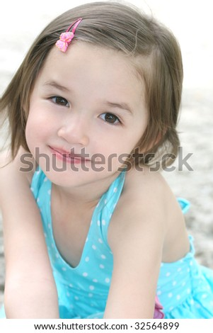 Portrait of a cute little toddler girl in blue dress
