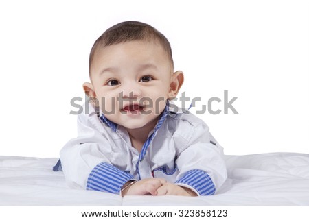 Portrait of a cute male baby lying on the bed, look at the camera and laughing, isolated on white