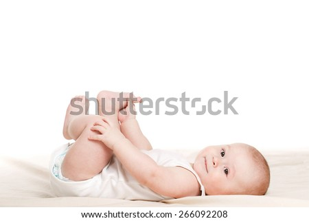 Portrait of a cute 3 months baby lying down on a blanket. Feeling dry and happy. Happy little baby smiling while laying on white background